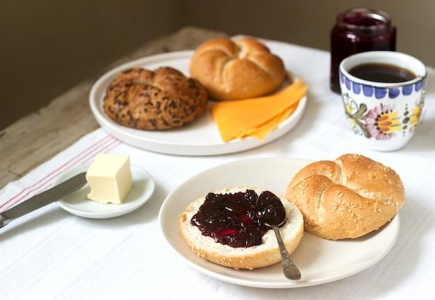 Frühstück mit kaiserbrötchen, johannisbeermarmelade, butter und käse sowie tee.