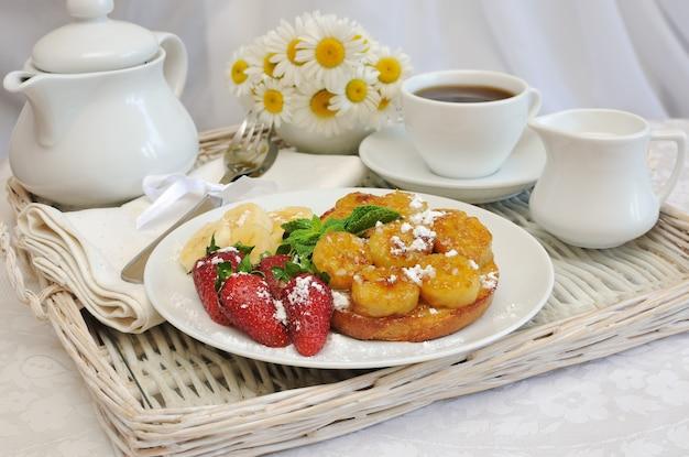 Frühstück mit karamellisierten bananen und erdbeeren auf einem tablett