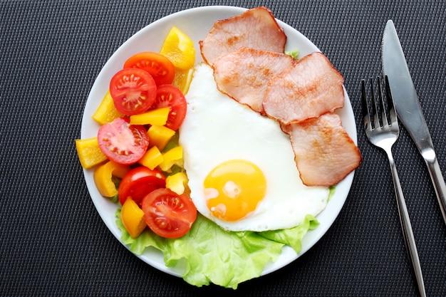 Frühstück mit ketogener ernährung, gesundem ernährungsprogramm - eier, schinken und frisches gemüse