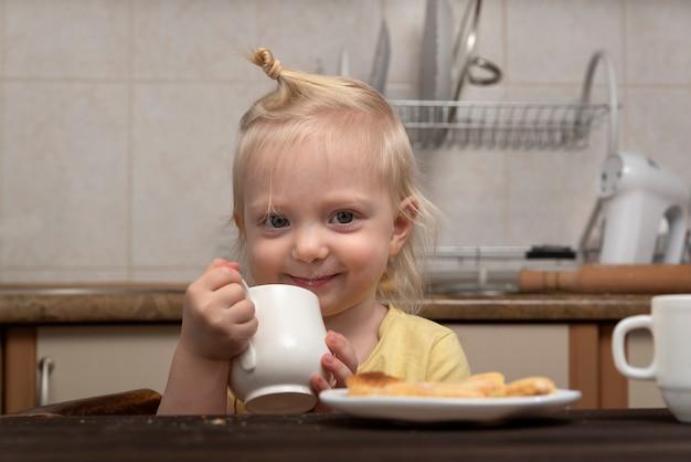 Frühstück mit kind. kleines mädchen trinkt eine milch. nettes blondes kind mit tasse in den händen in der küche.