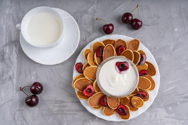 Frühstück mit mini-pfannkuchen mit kirsche und einer tasse milch auf betontisch