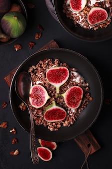 Frühstück mit müsli und feigen. schwarze teller mit einem frischen und gesunden frühstück. gesundes essen