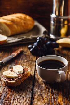 Frühstück mit obstsandwich und kaffee.