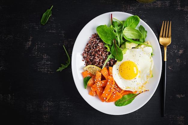 Frühstück mit quinoa, gebratenem kürbis in scheiben, avocado und spiegelei