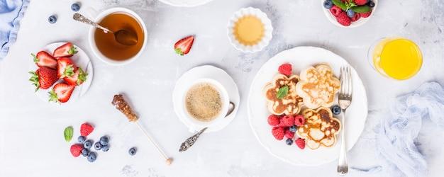 Frühstück mit schottischen pfannkuchen in blütenform, beeren und honig auf hellem holztisch