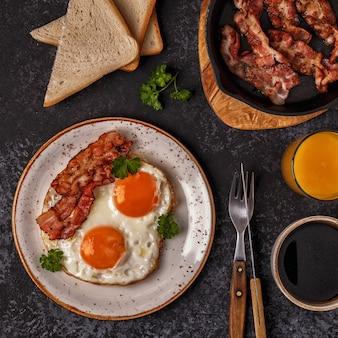 Frühstück mit speck, spiegelei, kaffee und orangensaft