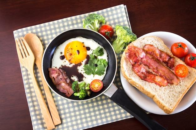 Frühstück mit spiegelei und speck in der dunklen wanne auf dem tisch