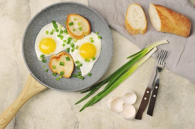 Frühstück mit spiegeleiern und frühlingszwiebeln und baguette auf grauer oberfläche