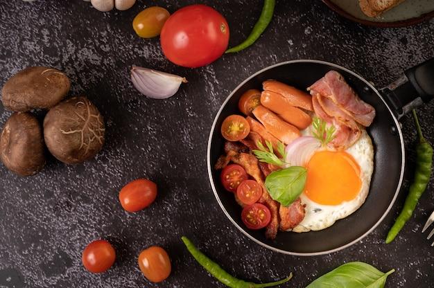 Frühstück mit spiegeleiern, wurst und schinken in einer pfanne mit tomaten. chili und basilikum