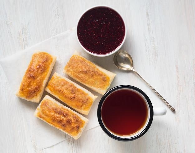 Frühstück mit süßen brötchen vom blätterteig, himbeermarmelade, tasse tee auf pergamentpapier.