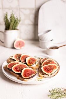 Frühstück mit süßen bruschettas mit feigen und honig auf einem weißen teller