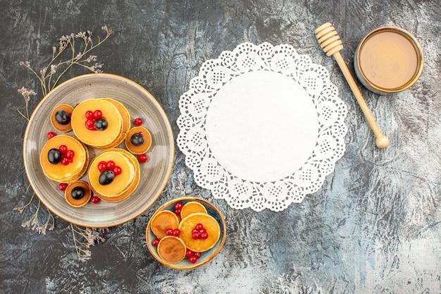 Frühstück mit süßen honigpfannkuchen in kleinen und großen tellern neben der serviette