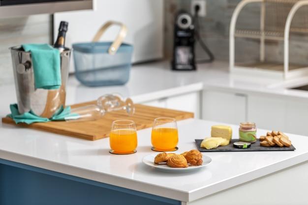 Frühstück mit toastbrötchen und käse in der küche. champagner im hintergrund.