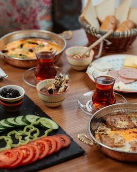 Frühstück mit verschiedenen speisen und schwarzem tee