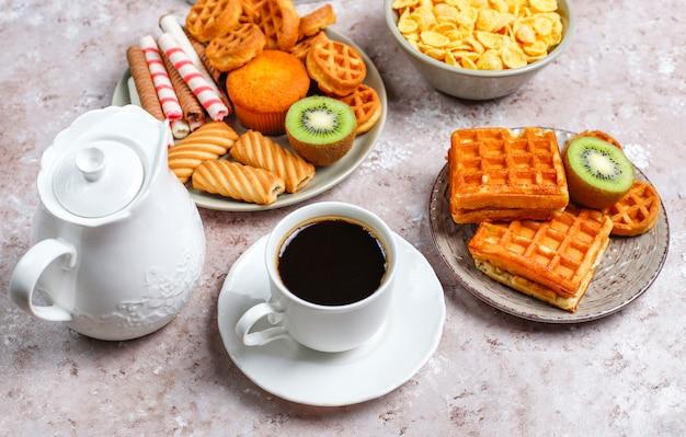 Frühstück mit verschiedenen süßigkeiten, waffeln, cornflakes und einer tasse kaffee, draufsicht