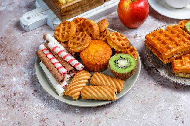 Frühstück mit verschiedenen süßigkeiten, waffeln, cornflakes und einer tasse kaffee