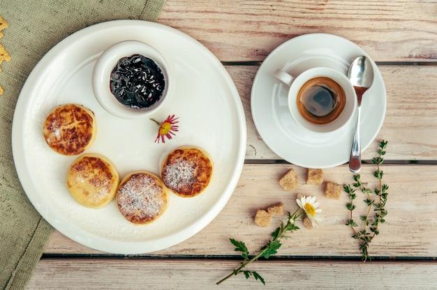 Frühstück mit vier käsepfannkuchen, schwarzem kaffee und johannisbeermarmelade