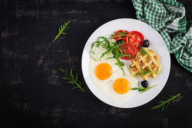 Frühstück mit zucchini-waffeln, spiegeleiern, tomaten, schwarzen oliven und rucola auf weißem hintergrund. vorspeisen, snacks, brunch. gesundes vegetarisches essen. draufsicht, overhead, textfreiraum