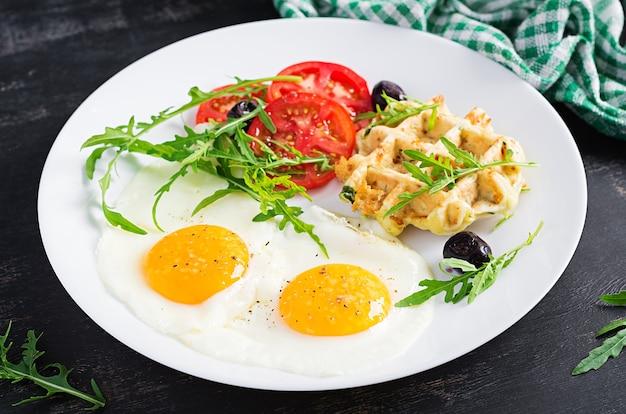 Frühstück mit zucchini-waffeln, spiegeleiern, tomaten, schwarzen oliven und rucola auf weißem hintergrund. vorspeisen, snacks, brunch. gesundes vegetarisches essen.