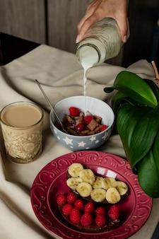 Frühstück, müsli mit milch, kaffee mit milch in einem facettierten glas, beterbrots mit schokoladenbutter, beeren und bananen
