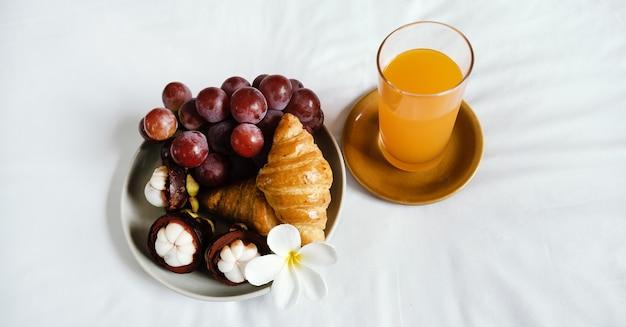 Frühstück, obst, croissants, orangensaft auf einem weißen bettlaken, gesundes lebensmittelkonzept.