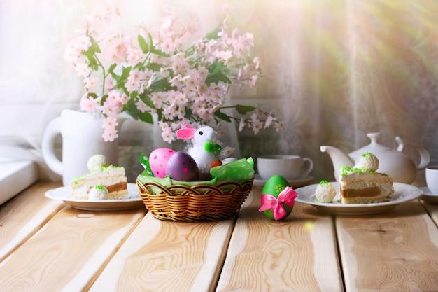 Frühstück oder brunch auf holztisch mit osterhasen, bunten eiern, ostergebäck und einer tasse tee. ostermorgen consept.