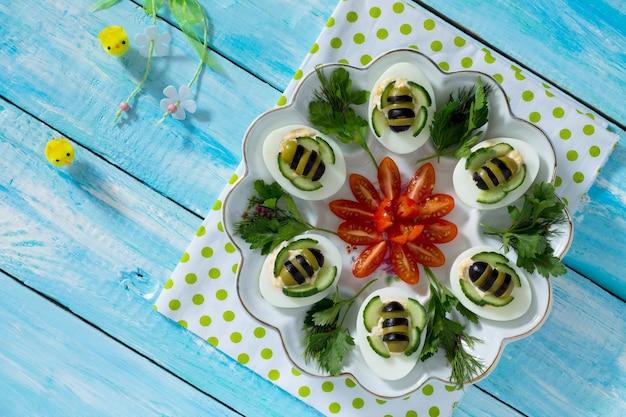 Frühstück oder mittagessen für kinder - hart gekochte eierbiene. frohe ostern essen für die kinder. draufsicht mit kopierraum.