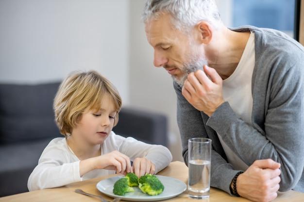Frühstück. reifer mann, der versucht, seinen sohn dazu zu bringen, gesund zu essen, während der junge unglücklich aussieht