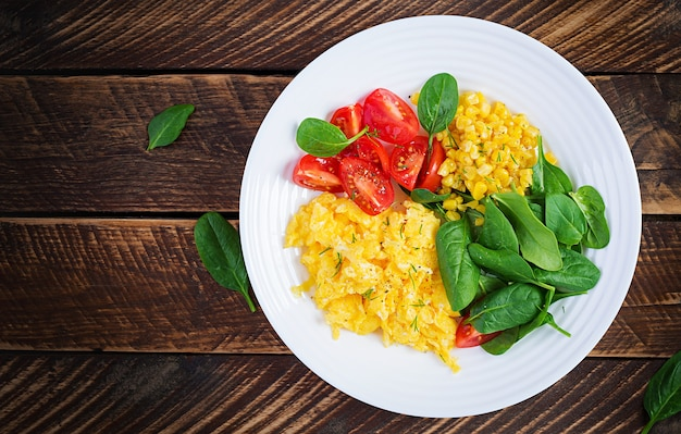 Frühstück. rührei mit kirschtomaten, spinat und mais.