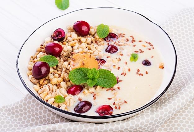 Frühstück, schüssel hausgemachtes müsli mit bananenpüree, erdnussbutter und frischen beeren
