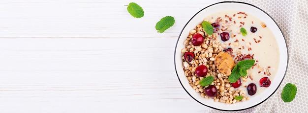 Frühstück. schüssel hausgemachtes müsli mit bananenpüree und frischen beeren. sitzordnung bei tisch. gesundes essen. draufsicht.
