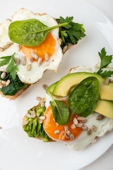 Frühstück . spiegeleier auf einem toastbrot mit avocado, spinat und samen auf einem weißen teller mit einer tasse tee. draufsicht.