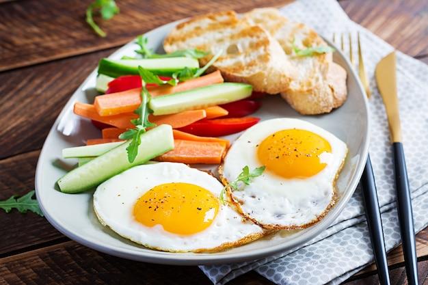 Frühstück. spiegeleier mit frischer karotte, gurke, paprika und toast auf holz