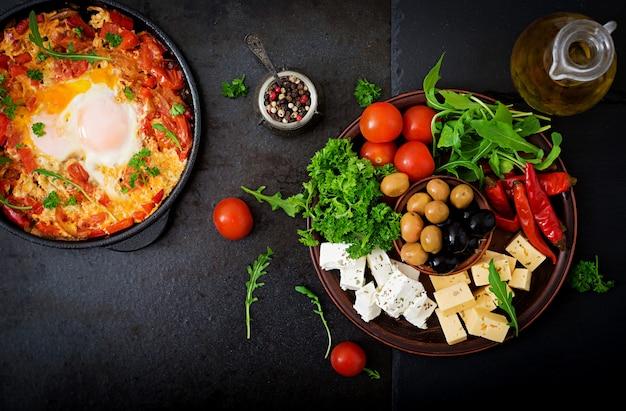 Frühstück. spiegeleier mit gemüse. shakshuka in einer pfanne auf einem schwarzen im türkischen stil.