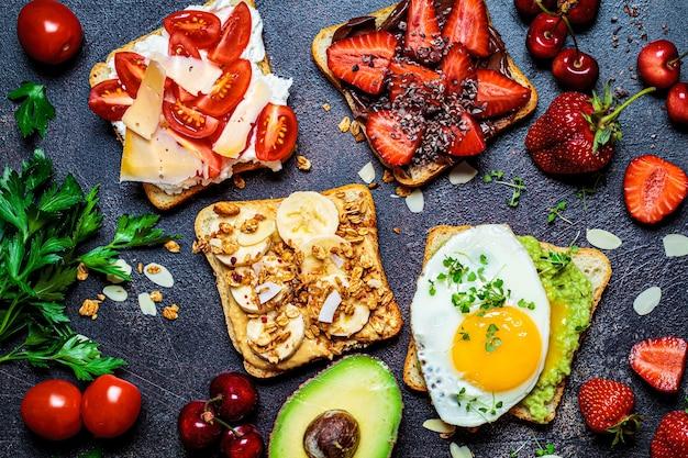 Frühstück verschiedene toasts mit beeren, käse, ei und obst, dunkler hintergrund, draufsicht. frühstückstischkonzept.