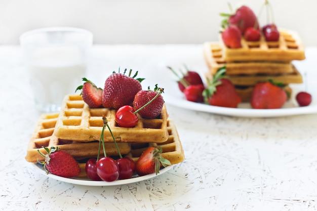 Frühstück. waffeln mit erdbeeren und kirschen und milch auf einer weißen platte