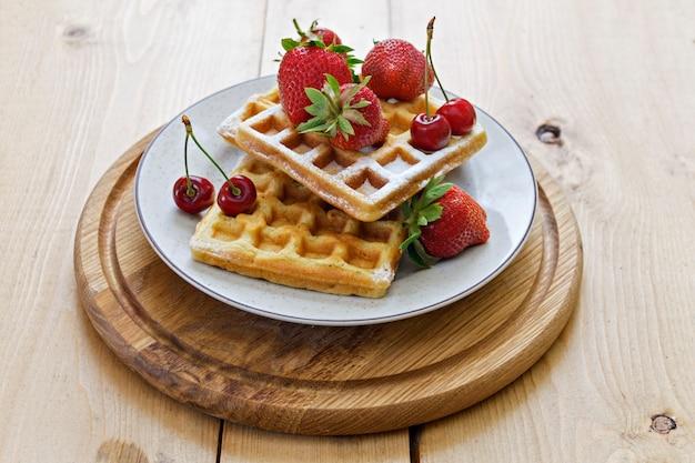 Frühstück. wiener waffeln mit erdbeeren und kirschen auf einem holzbrett. frühling