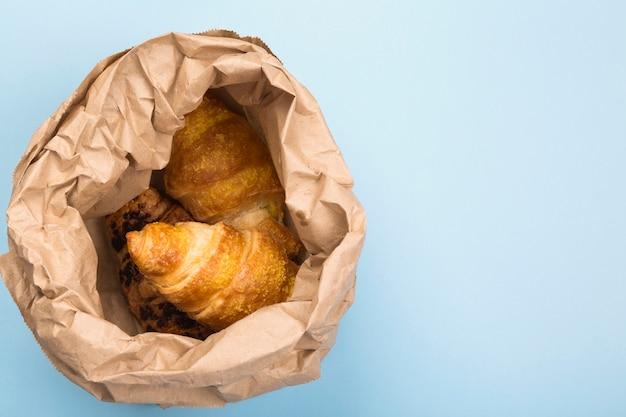 Frühstück zum mitnehmen. croissants in papierverpackung auf blauem hintergrund. lieferung von produkten. draufsicht, kopierraum