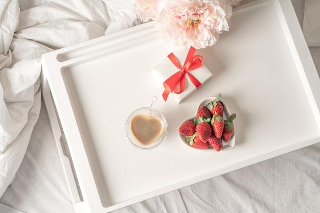 Frühstück zum valentinstag mit kaffee und erdbeeren.