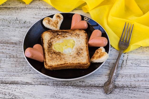 Frühstück zur feier des valentinstags - toast mit rührei in form von herzen, würstchen auf einem teller und einer gabel