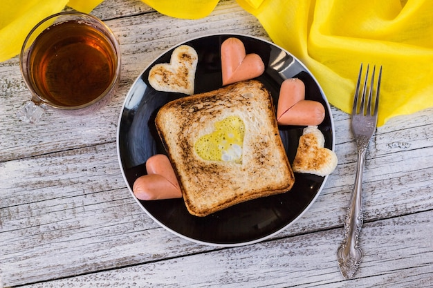 Frühstück zur feier des valentinstags - toast mit rührei in form von herzen, würstchen und tee
