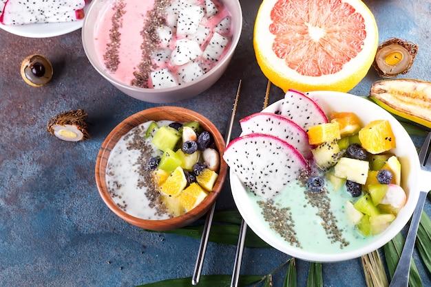 Frühstücken sie grüne jogurtschüssel, die mit pitaya, ananas, chia samen und beeren mit palmblatt auf steinhintergrund, draufsicht überstiegen wird