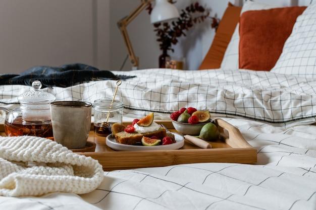 Frühstücken sie im bett mit gebäck und frischen früchten, schwarzer tee