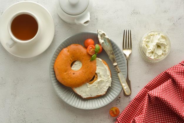 Frühstücken sie mit bageln und käse, kirsche, basilikum, teeschale. gesundes essen.