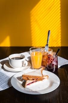 Frühstücken sie mit erdnussbutter und stau und einem tasse kaffee auf einer sonne des holztischs morgens