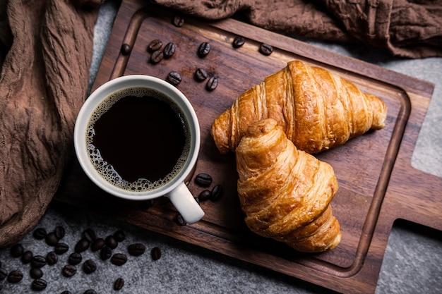 Frühstücken sie mit frischen hörnchen und schale schwarzem kaffee auf hölzernem brett