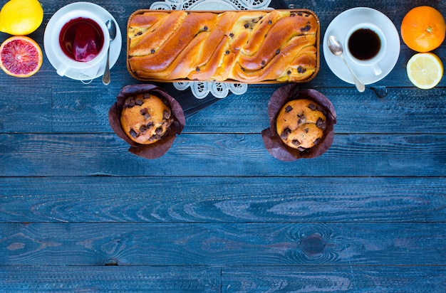 Frühstücken sie mit kaffee und tee mit unterschiedlichem gebäck und früchten auf einem holztisch