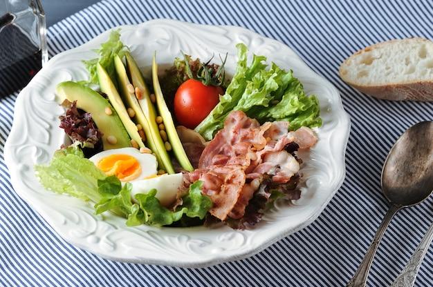 Frühstücken sie mit speck, avocado, ei und salat auf einer serviette