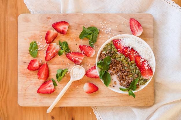 Frühstücks-beeren-smoothie-bowl mit erdbeer-kürbiskernen-kokos-müsli und frischer minze