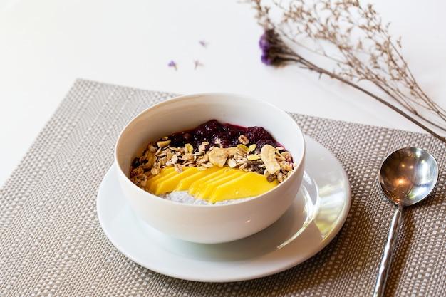 Frühstücks-beeren-smoothie-schüssel mit heidelbeer-, mandel-, bananen- und chiasamen.